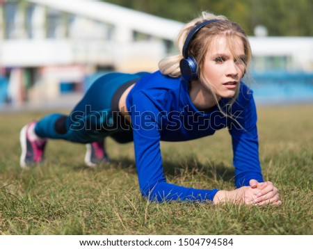 Fit girl in headphones doing plank exercise outdoor in the park warm summer day. Concept of endurance and motivation.