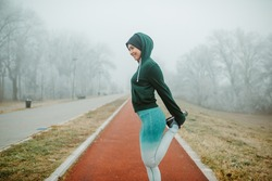 Fit girl is warming up for jogging. Girl is wearing cap, hoodie and tights.