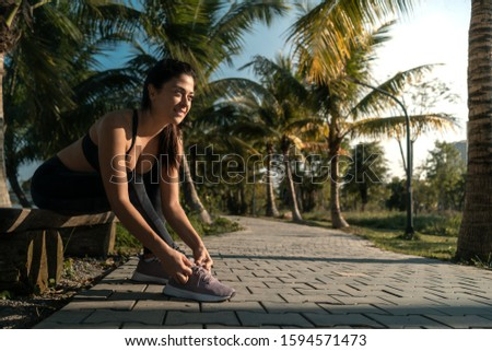 Fit girl tying running sneakers getting ready for jogging in nature