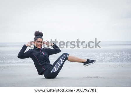 Fit girl working out on cold day at the beach #300992981