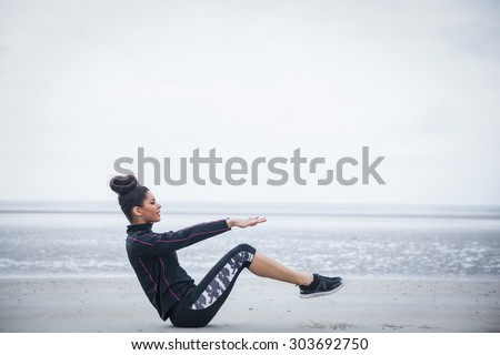 Fit girl working out on cold day at the beach #303692750