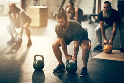 Fit group of people working out with weights together during an exercise class at a gym