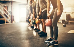 Fit group people in exercise gear standing in a row holding dumbbells during an exercise class at the gym