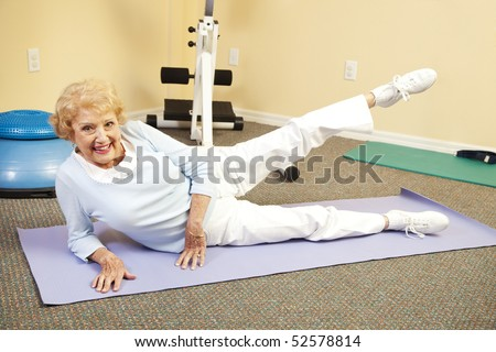 Fit happy senior woman doing stretching exercises on her yoga mat.