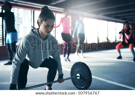 Fit healthy woman lifting a weight barbell from floor, exercising with group of people outside urban setting #507956767