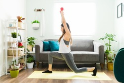 Fit hispanic woman using dumbells in her home workout. Young woman doing leg plunges and lifting weights in her living room home