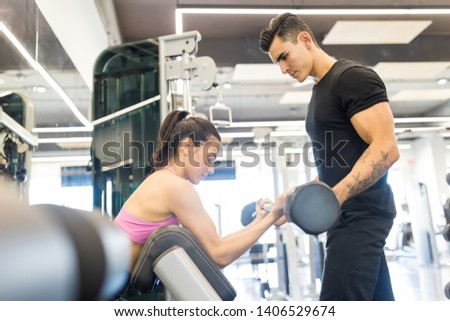 Fit male coach helping woman in exercising with barbell at health club