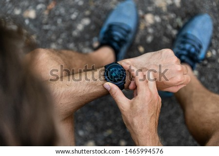 Fit man checking smart watch wearable technology sport smartwatch on fitness run walk outside. Top view from above with running shoes in street. Stockfoto ©