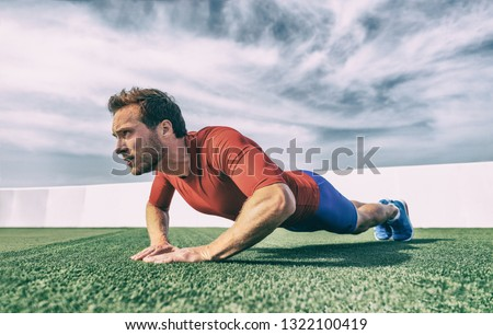 Fit man doing diamond hand push ups exercise at outdoor gym. Core body workout athlete planking or doing pushup on grass.