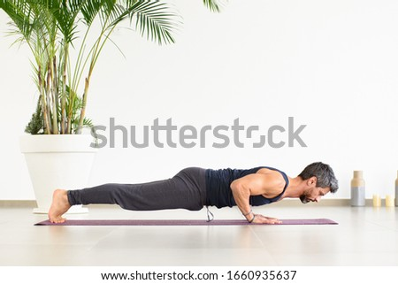 Fit man doing Yoga chaturanga push-ups during his workout in a high key gym with potted palm in a low angle side view in a health and fitness concept Foto stock ©