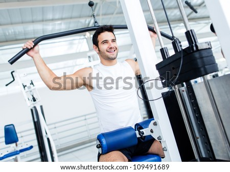 Fit man exercising at the gym on a machine stock photo