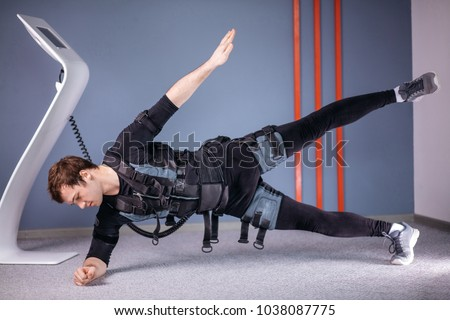Fit man in Electrical Muscular Stimulation suits doing side plank exercise. EMS