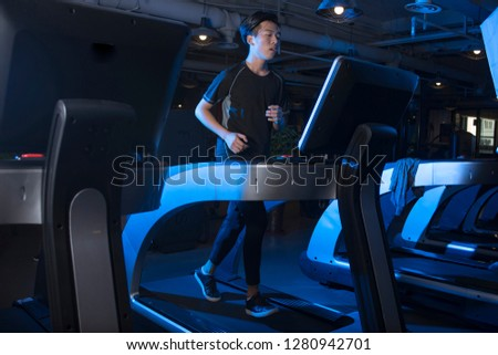 Fit man jogging on the treadmill at the gym  #1280942701