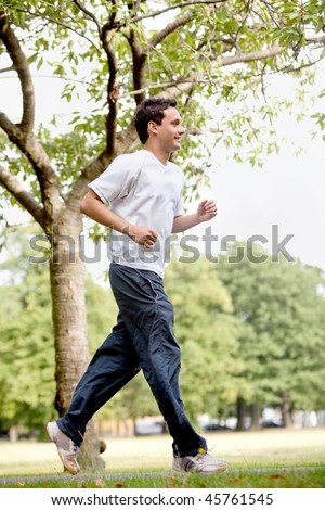 Fit man jogging outdoors at the park