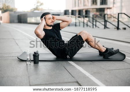 Fit man pumping press lying on black yoga mat. Muscular man doing his favorite morning exercise. Black sport clothes. Fit happy man doing fitness exercises outdoors. Street on background.