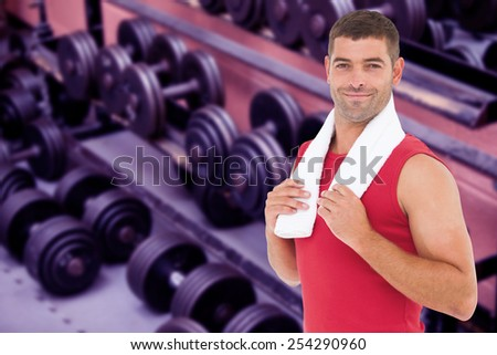 Fit man smiling at camera against collection of barbells
