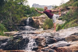 Fit man standing on a rock doing the dancer pose while practicing yoga by a waterfall in a forest