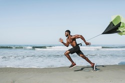 Fit man with a running parachute at the beach
