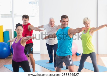 Shutterstock Fit men and women doing warrior pose in yoga class