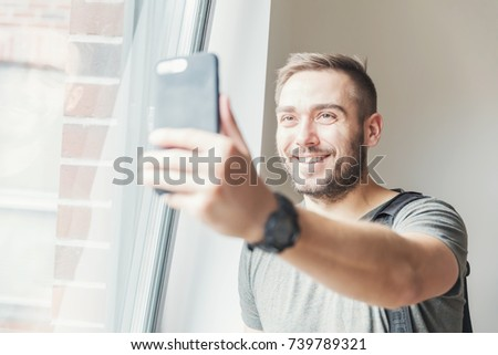 Fit millenial man taking a selfie in the daylight, holding a phone in his hand.