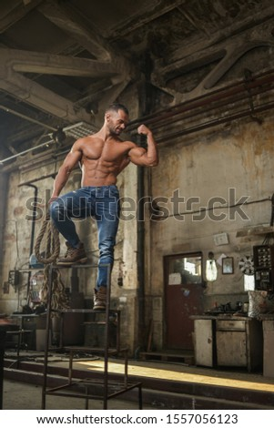 Fit muscled half naked man at work in an old factory.