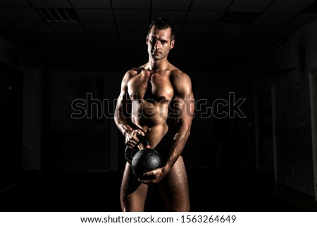 Fit muscular bodybuilder man posing on dark background