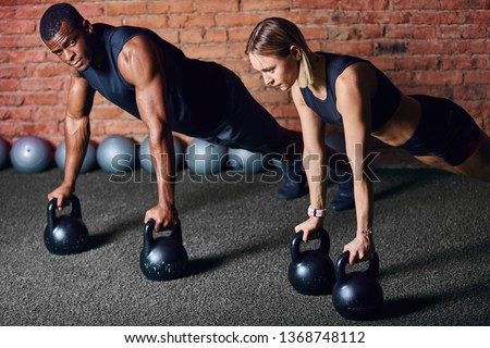 Fit muscular interracial couple in black sportswear doing plank on kettlebells in crossfit functional training in gym over red brick background.