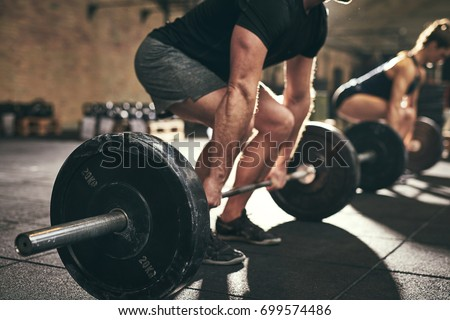 Fit people doing deadlift exercise in gym. Horizontal indoors shot