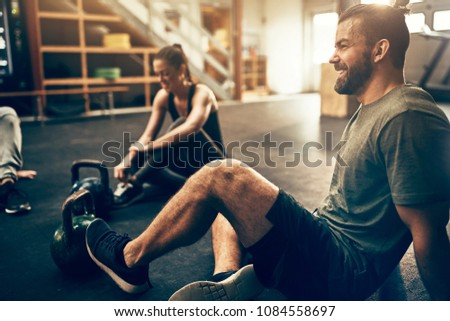 Fit people in exercise gear sitting on the floor of a gym laughing together after a workout