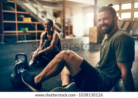 Fit people in exercise gear sitting together on the floor of a gym laughing together after a workout