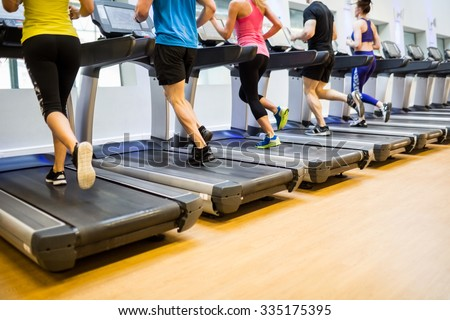 Fit people jogging on treadmills at the gym
