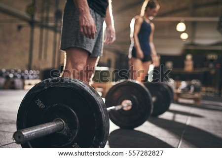 Fit people standing at barbells before exercise. Horizontal indoors shot