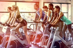 Fit people working out at spinning class in the gym