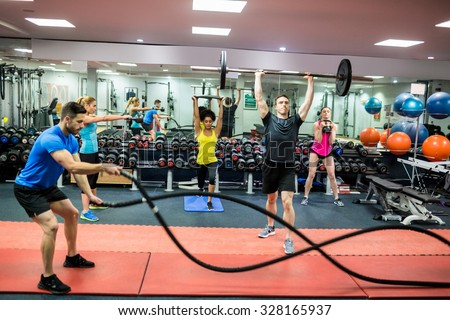 Fit people working out in weights room at the gym
