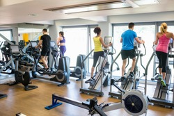 Fit people working out using machines at the gym