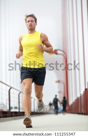 Fit runner running outside. Young male fitness model training in yellow on Golden Gate Bridge, San Francisco, California, USA.