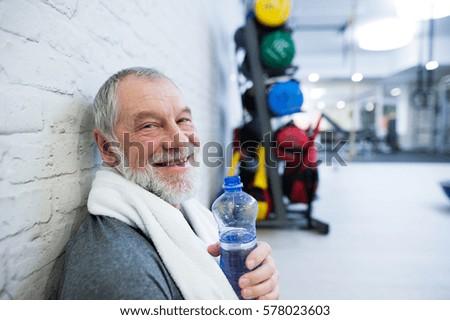 fit senior man in gym resting...