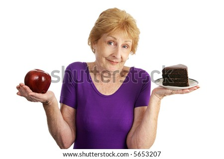 Fit senior woman choosing between chocolate layer cake and an apple for dessert.  Isolated on white.
