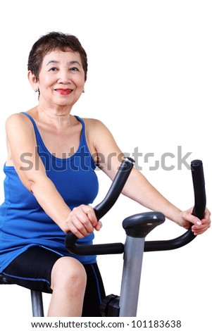 Fit senior woman exercising on a stationary bicycle.