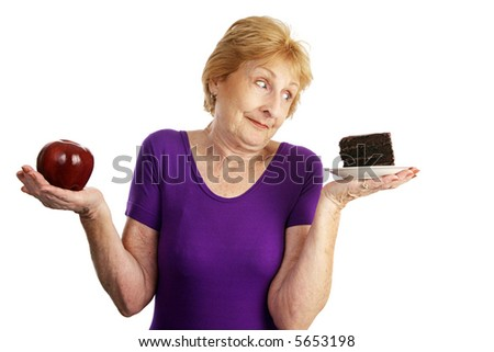 Fit senior woman making food choices.  She is unable to resist the chocolate cake.  Isolated on white. - stock photo