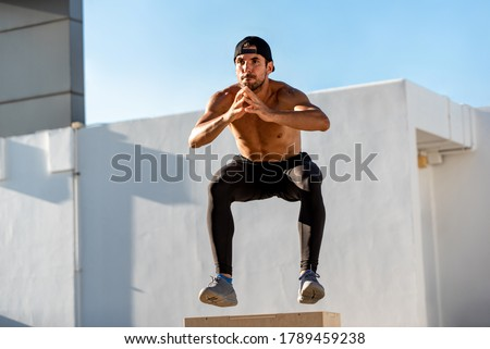 Fit shirtless athletic man jumping up to plyometric wood box outdoors on building rooftop, home workout exercise concept Stockfoto ©