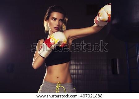 Fit slim young beautiful brunette woman boxing in sportswear. Dark dim light. Toned image