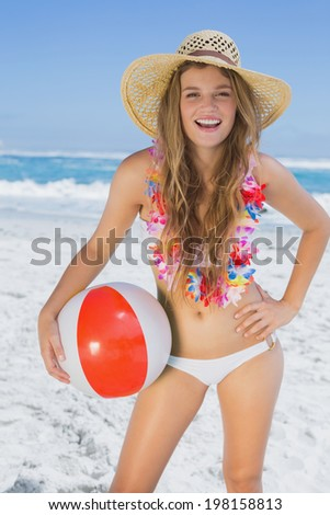Fit smiling blonde in white bikini and straw hat holding beach ball on a sunny day