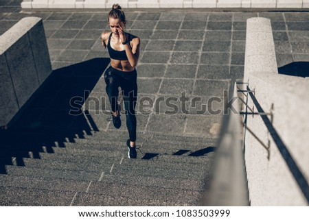 Fit sportswoman running up the steps. Female runner exercising on staircase outdoors. #1083503999