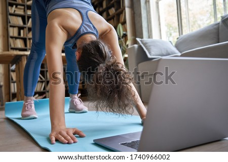 Fit sporty hispanic girl doing online yoga exercise stretch on mat at home. Active young healthy latin woman enjoy sport pilates physical fitness training on laptop computer watching video class guide