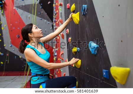 Fit sporty woman looking up at rock climbing wall at the gym and training #581401639