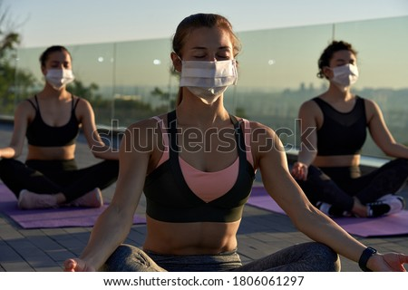 Fit sporty young woman wear medical face mask for safety meditating keeping social distance with female friends practicing yoga fitness exercise together on sunrise at retreat group class outdoors.