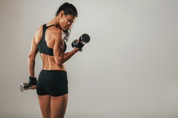 Fit strong young woman lifting weights working out with dumbbells standing with her back to the camera flexing her arm on grey with copy space