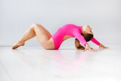 Fit supple athletic woman in a trendy pink leotard doing a back stretch on a white wooden floor in a high key gym in a health and fitness concept with copyspace