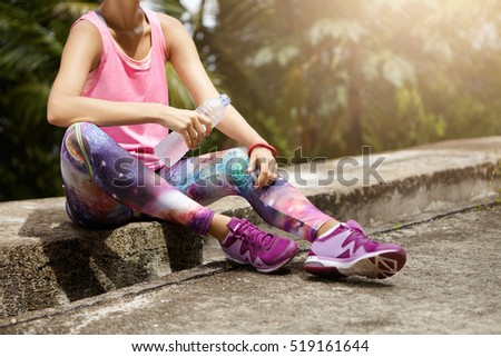 Fit woman athlete drinking water out of plastic bottle after hard running workout. Cropped shot of female runner in pink top and space print leggings resting after successful jogging exercise outdoors